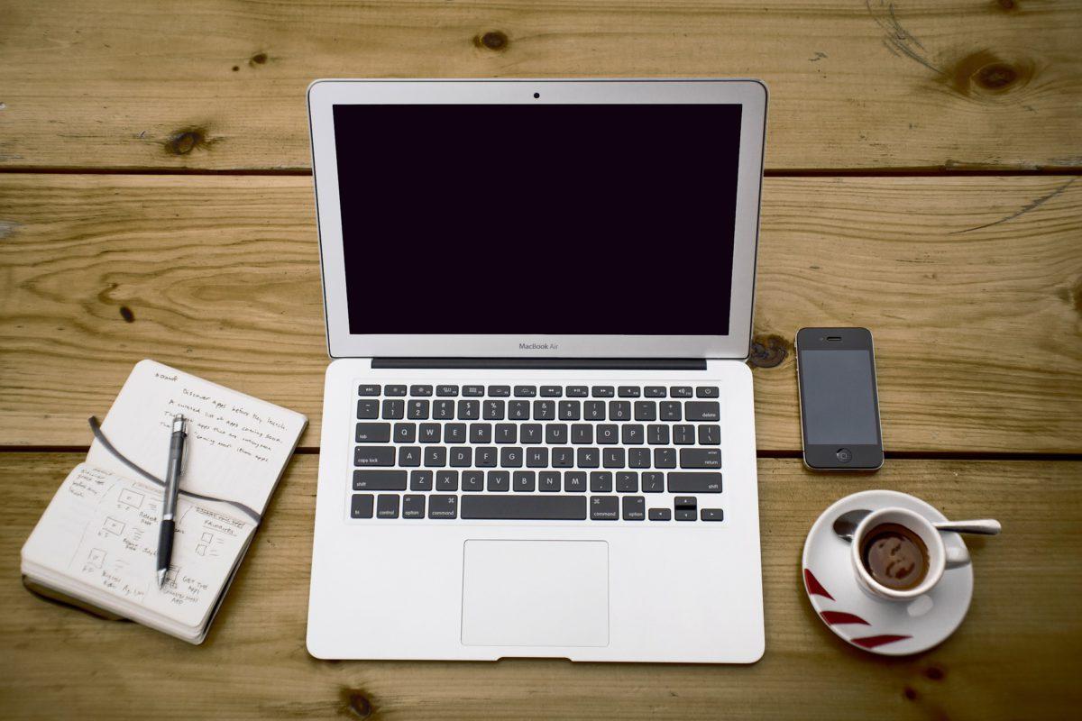 Werkopstelling: laptop, koffie, telefoon, notitieblok